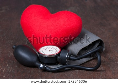 Medical, measure blood pressure with red heart on wood table - stock photo