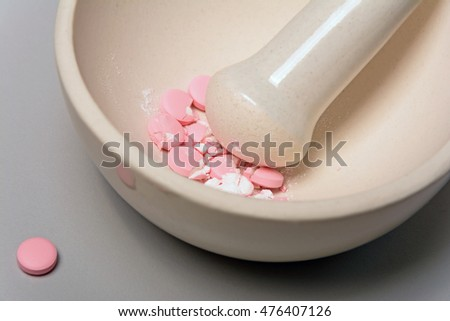 Medical mortar and pink pills on a gray background