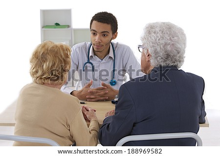 Medical mulatto doctor and elderly couple patient. at doctor office - stock photo