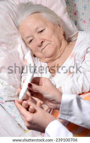 Medical nurse measuring the blood sugar level of old patient - stock photo