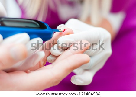 Medical nurse measuring the blood sugar with modern medicine - stock photo