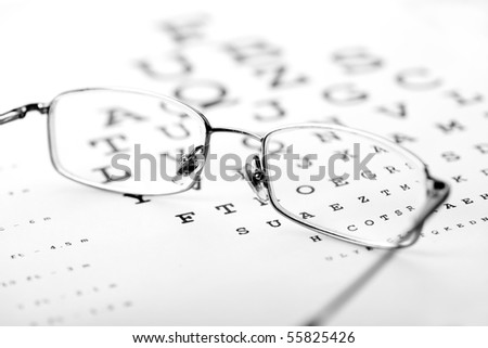Medical optics concept with glasses on eye chart - monochrome - stock photo