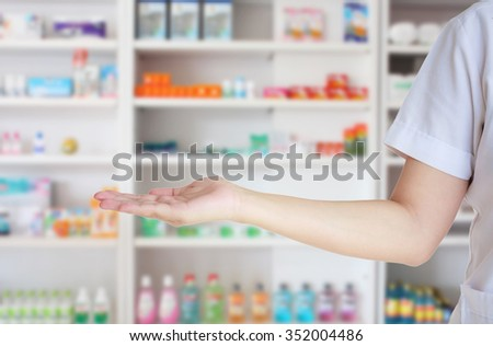 medical pharmacist woman presenting and showing copy space for product or text with blur shelves of drugs in the pharmacy - stock photo