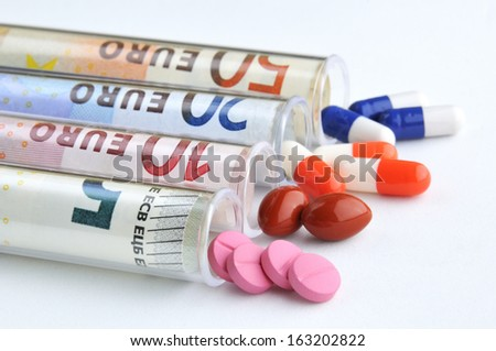 medical pills and tablets in euro bank notes money as a symbol of health care costs - stock photo