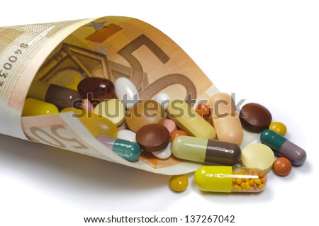 medical pills in rolled 50 euro bank note as symbol for high costs - stock photo
