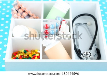 Medical pills,stethoscope,  ampules in wooden box, on color background