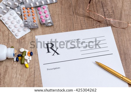 Medical prescription and drugs and pen on table - stock photo