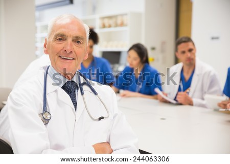 Medical professor smiling at the camera during class at the university - stock photo