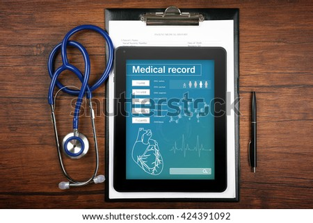 Medical record on tablet screen with stethoscope on wooden background - stock photo