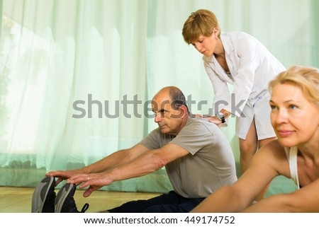 Medical staff at gym helping pensioners couple to take correct position. Focus on man