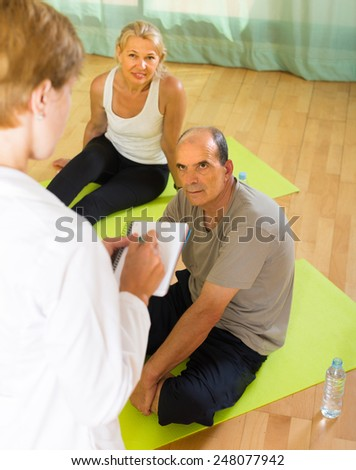 Medical staff watching yoga class for pensioners at gym. Focus on man  - stock photo