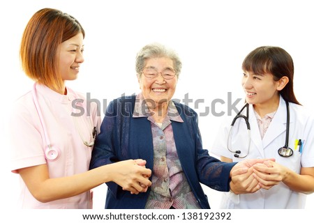 Medical staff with senior woman - stock photo