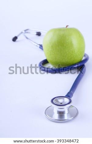 Medical stethoscope and apple isolated on white background - stock photo