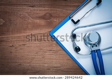 Medical stethoscope and clip board on vintage wooden pine table medicine concept  - stock photo