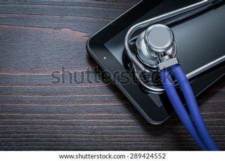 Medical stethoscope and digital tablet on vintage wooden board medicine concept  - stock photo