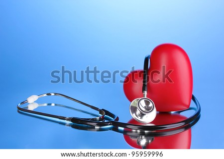 Medical stethoscope and heart on blue background - stock photo