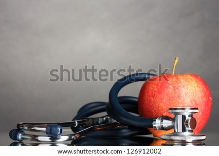 Medical stethoscope and red apple on grey - stock photo