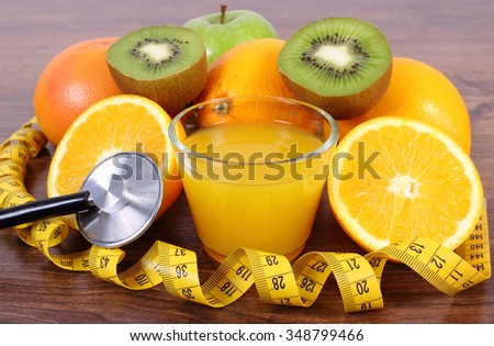 Medical stethoscope and tape measure with fresh ripe fruits and glass of juice on wooden surface plank, grapefruit orange kiwi apple, healthy lifestyles and nutrition - stock photo