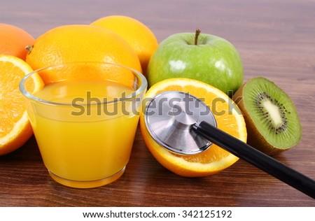 Medical stethoscope, fresh ripe fruits and glass of juice on wooden surface plank, grapefruit orange kiwi apple, healthy lifestyles nutrition and strengthening immunity - stock photo