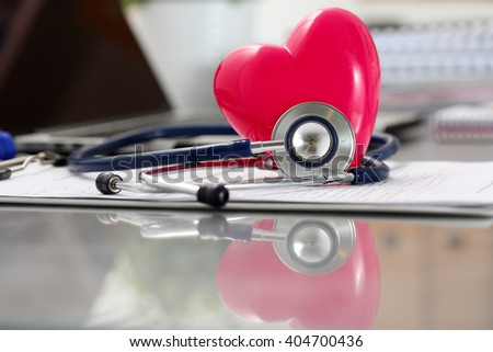Medical stethoscope head and red toy heart lying on cardiogram chart closeup. Cardio therapeutist, physician make cardiac physical, heart rate measure, arrhythmia, resuscitation and pacemaker concept - stock photo