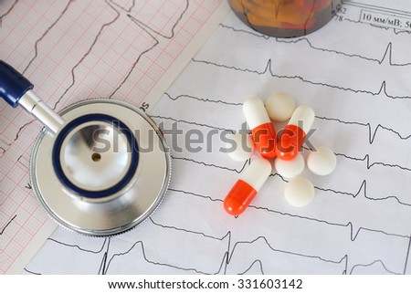 Medical stethoscope head lying on cardiogram chart with pile of pills closeup. Cardiology care, health, protection, prevention and help. Healthy life or insurance concept - stock photo