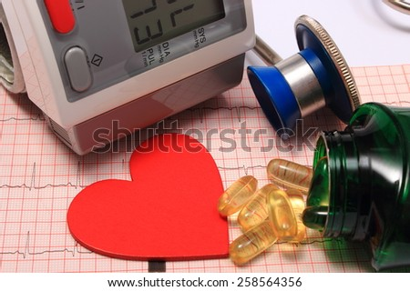 Medical stethoscope, instrument for measuring blood pressure, red heart shape and tablets on electrocardiogram graph, ekg heart rhythm, medicine concept - stock photo