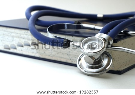 Medical stethoscope sitting besides a medical book.