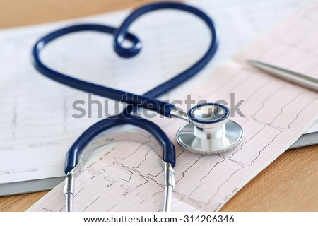 Medical stethoscope twisted in heart shape lying on cardiogram chart closeup. Medical help, prophylaxis, disease prevention or insurance concept. Cardiology care, health, protection and prevention - stock photo