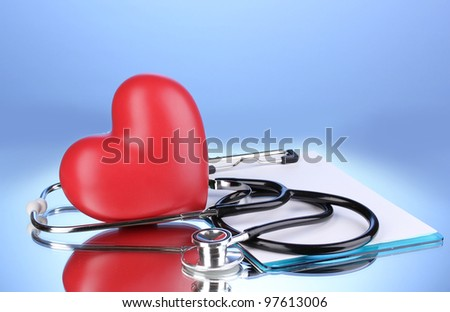 Medical stethoscope with clipboard and heart on blue background - stock photo
