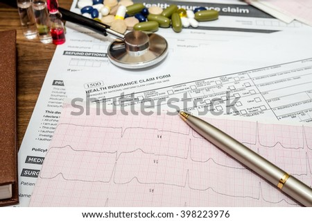 Medical still life with patient health information, cardiogram, pills,  stethoscope on wooden table - stock photo