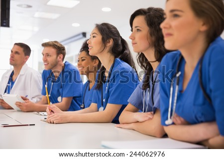 Medical students listening sitting at desk at the university - stock photo