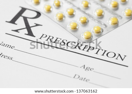 Medical stuff - blank prescription and pills on table - stock photo