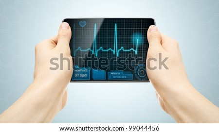 Medical tablet PC showing cardiogram on display. - stock photo