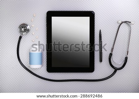 Medical tablet with stethoscope on white background