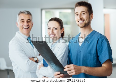 Medical team composed of doctors and surgeon smiling at camera and examining a patient's x-ray image of human spine, teamwork and assistance concept - stock photo