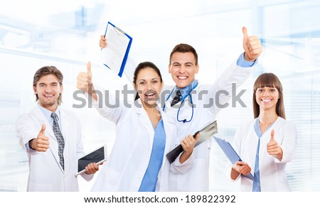 medical team doctor happy smile excited, hold thumb up finger gesture wear white coat, group of people celebrating in hospital