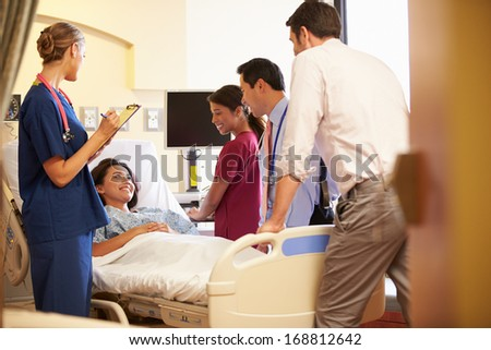 Medical Team Meeting Around Female Patient In Hospital Room - stock photo