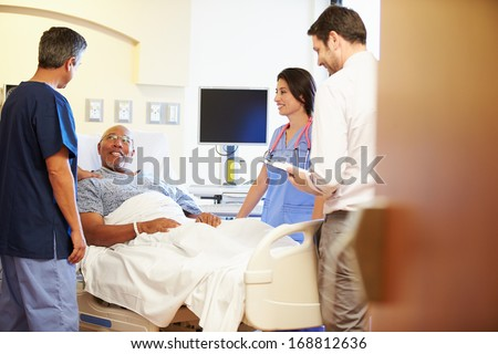 Medical Team Meeting With Senior Man In Hospital Room - stock photo