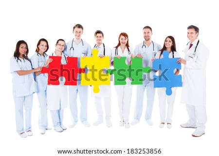 Medical team of a large group of diverse doctors  physicians and nurses in white uniforms standing in a row holding colorful puzzle pieces conceptual of teamwork  challenge and problem solving - stock photo