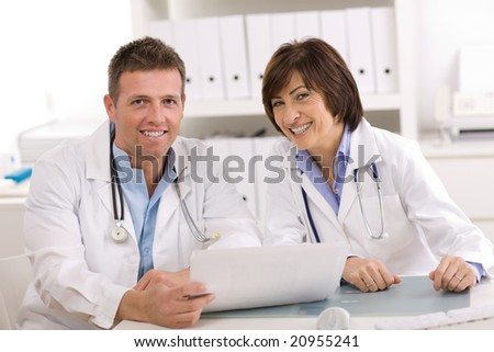 Medical team of male and female doctors sitting at desk.
