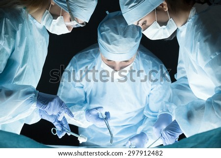 Medical team performing operation. Group of surgeon at work in operating theatre - stock photo