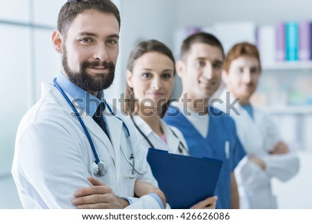 Medical team posing at the hospital they are standing and looking at camera, healthcare and teamwork concept