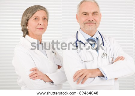 Medical team senior male doctor with professional female colleague portrait
