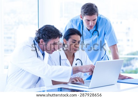 Medical team using laptop in the hospital - stock photo