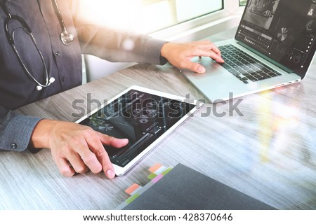 Medical technology concept. Doctor hand working with modern digital tablet and laptop computer with medical chart interface, Sun flare effect photo - stock photo
