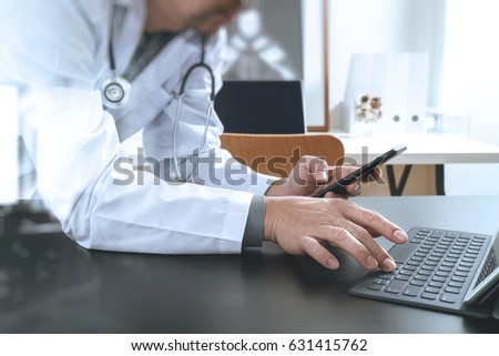 Medical technology concept. Doctor working with smartphone and stethoscope and digital tablet computer in modern office at hospital