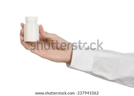 Medical theme: doctor's hand holding a white empty jar of pills on a white background - stock photo