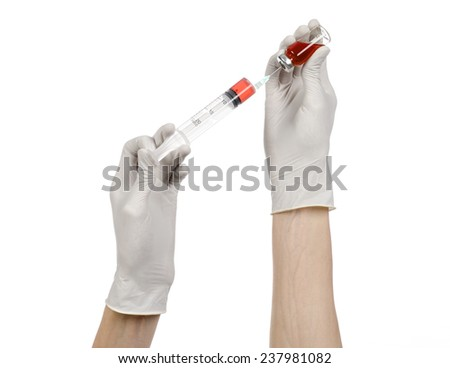 Medical theme: doctor's hand in a white glove holding a syringe and picking up of red liquid for injection ampules on a white background