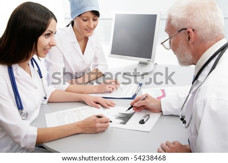 Medical theme: doctors are studying a medical report. - stock photo