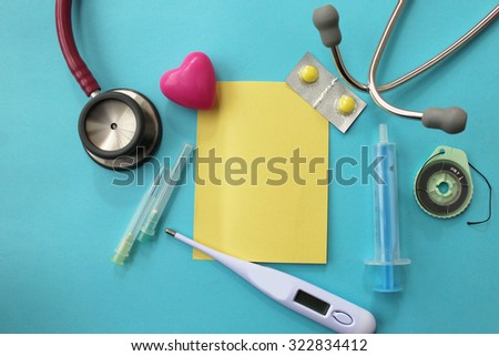 Medical theme -pill, syringe, needle, medical thermometer, surgical thread, stethoscope and sticky note - copy space on pink background - stock photo